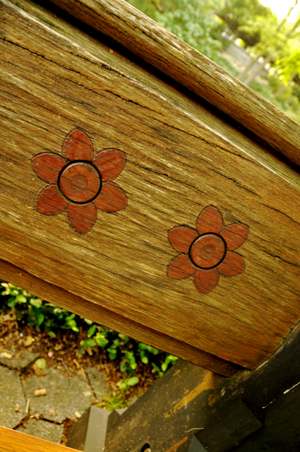 carved red flowers on a wooden bench