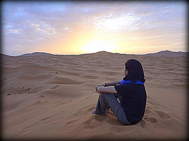 sunrise over the Sahara Desert: it's not obvious here, but I am sitting on top of a very tall sand dune.