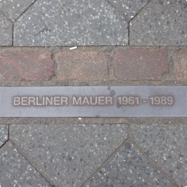 plaque near Checkpoint Charlie signifying where the Berlin wall stood.  If you can read the words right side up then you're standing on the East Side.  If you're reading it backwards then you are standing on the West Side.